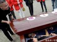 大街上擺放著兩口棺材,路人卻排長龍,只為躺進棺材裡!